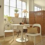 tavolo tondo in plastica bianca con sedie bianche e paravento in tessuto intrecciato