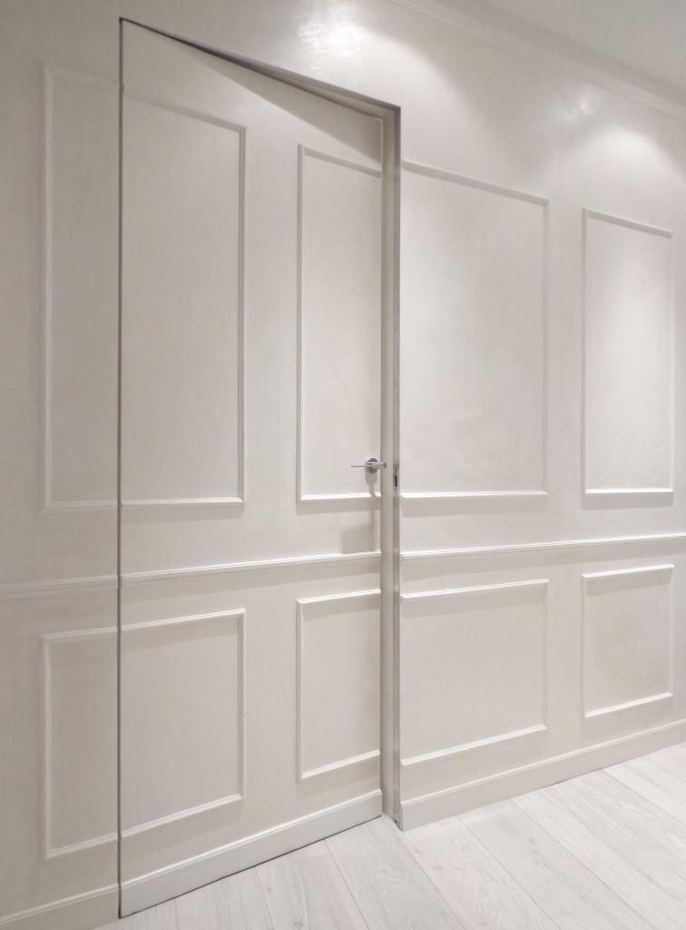 Come arredare una casa vacanze in total white con il dettaglio della porta battente della camera da letto