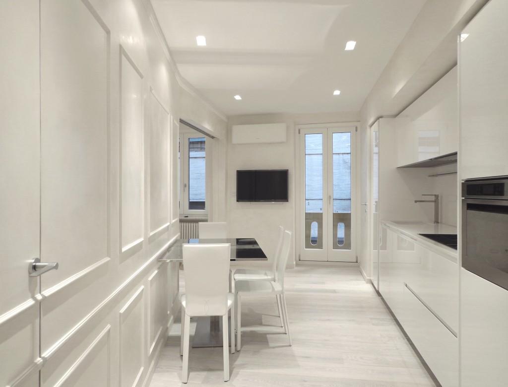 Vista della cucina in laccato lucido bianco con tavolo da pranzo e boiserie bianca