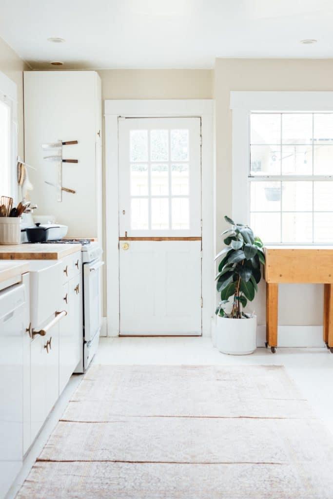 cucina in stile country con porta d'ingresso bianca e tappeto beige