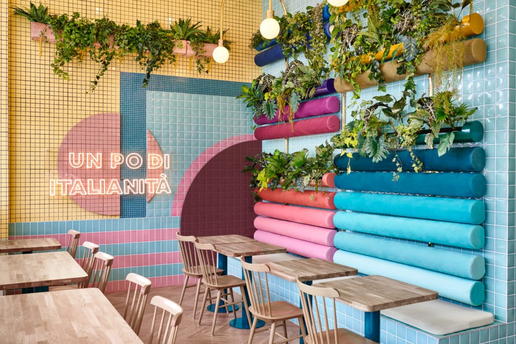 interno del ristorante Piada con dettaglio su tavoli e sedie in legno e panche azzurre e rosa