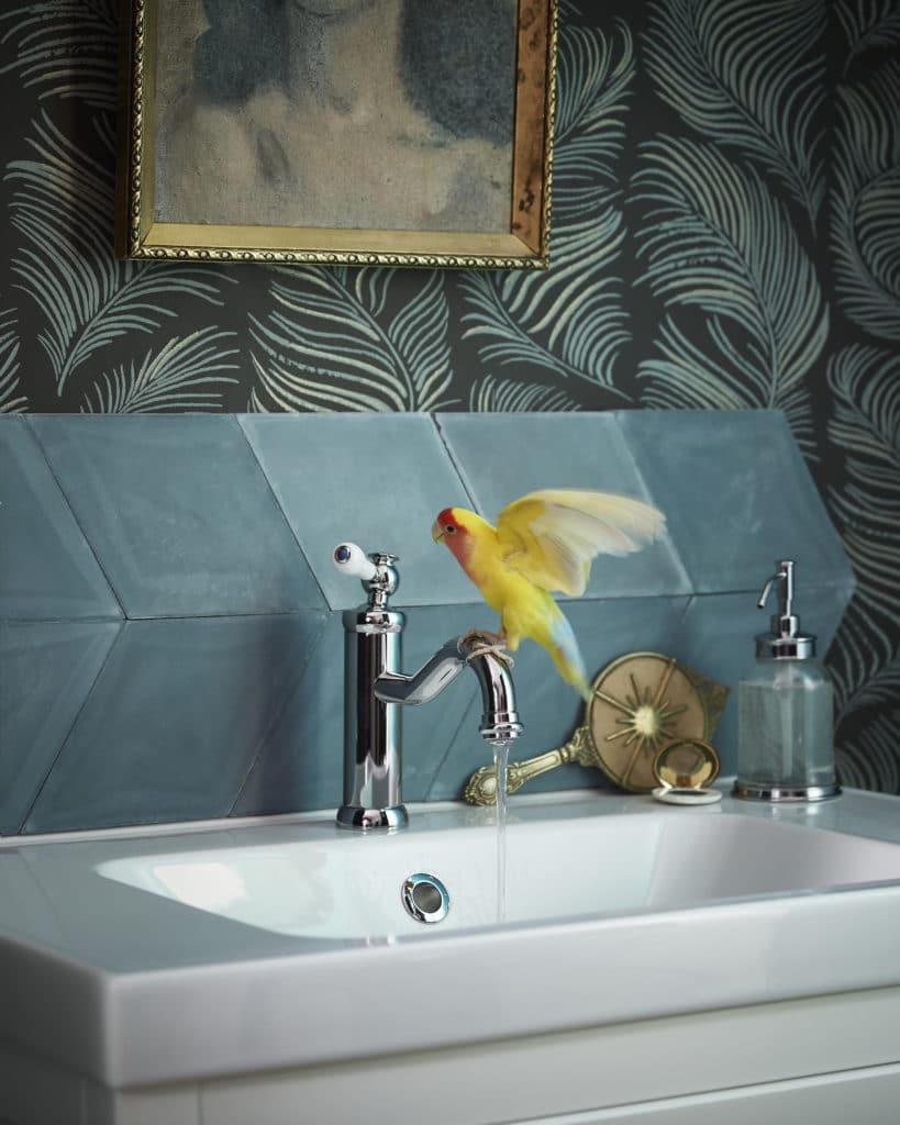 Dettaglio di lavandino da appoggio con piastrelle in blu ottanio e carta da parati a tema tropicale con canarino appoggiato al rubinetto.