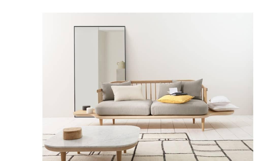 Soggiorno in stile minimal con divano a due posti con struttura in lengo chiaro, tavolino in marmo, grande specchio e tappeto a decoro geometrico.