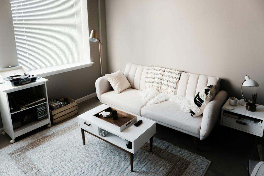 Vista dall'alto di un divano a tre posti bianco con tavolini da caffé laccati bianchi, tappeto in tessuto naturali chiaro e mobile porta giradischi.