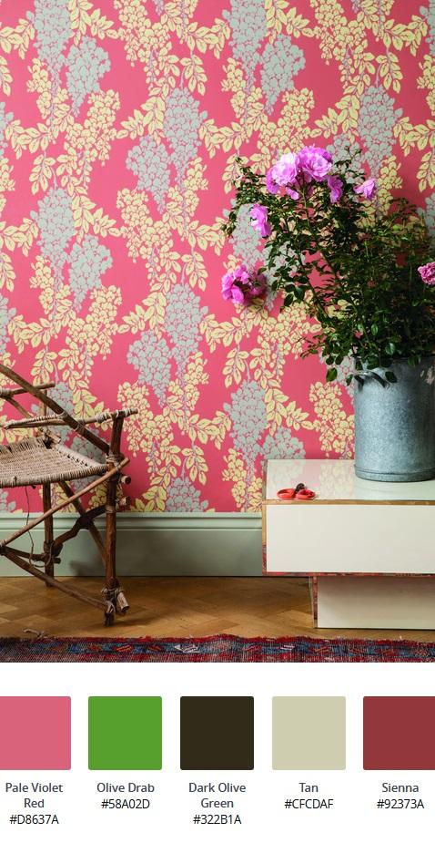 Cos'è lo stile d'arredo massimalista: interno con carta da parati floreale fucsia, sedia in vimini, tavolo basso laccato lucido bianco, vado di fiori in allumimio e tappeto rosso e blu