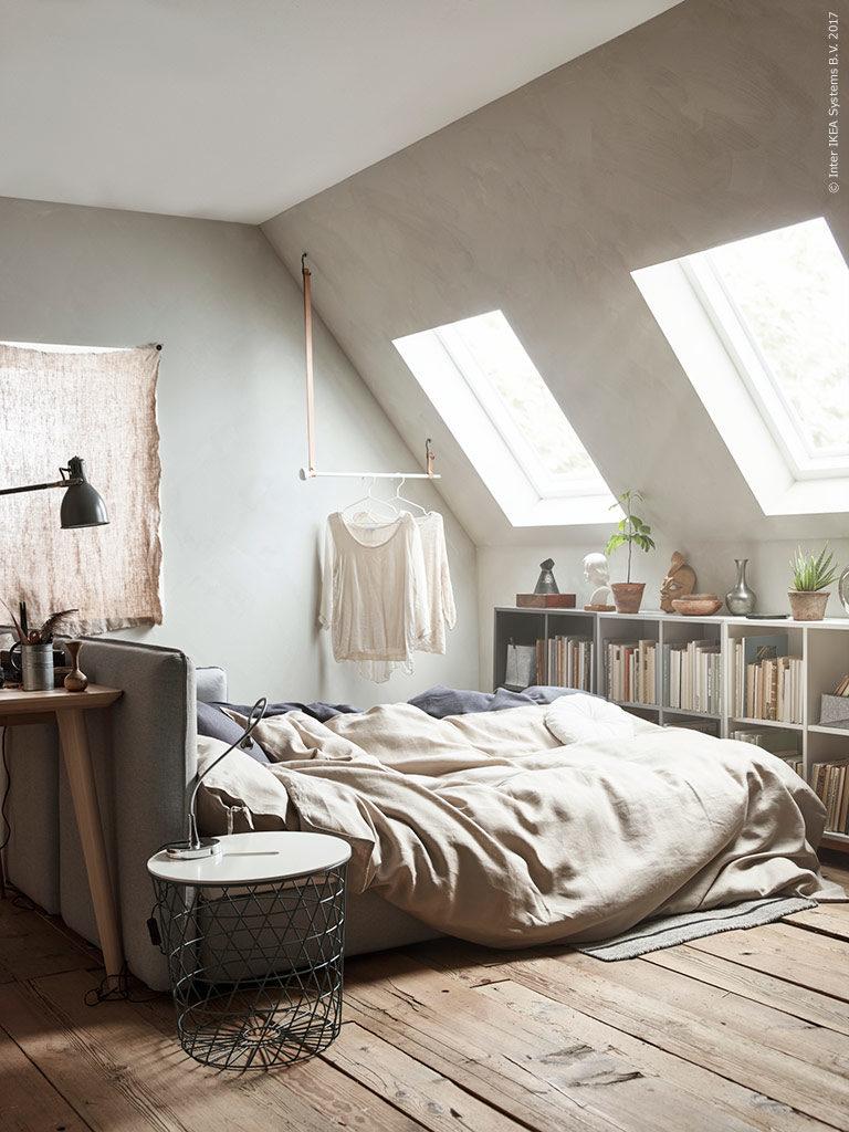 camera da letto con tetto spiovente e librerie sotto finestra
