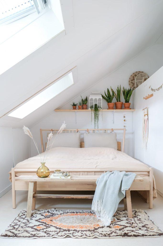 camera da letto in mansarda con tetto e pareti bianche e letto in legno chiaro