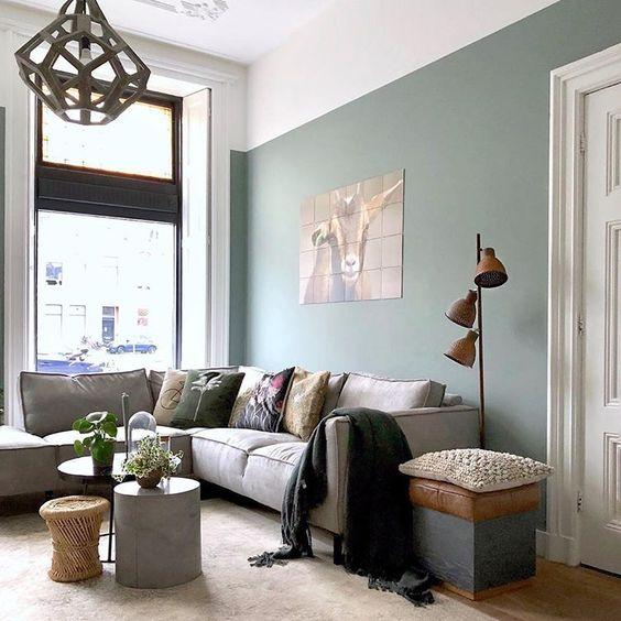 soggiorno arredato nei toni del verde con divano ad angolo grigio