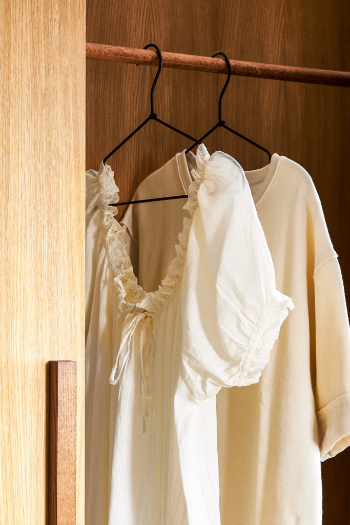 Vestiti bianchi appesi su tubo appendi abiti in legno all'interno di armadio in legno