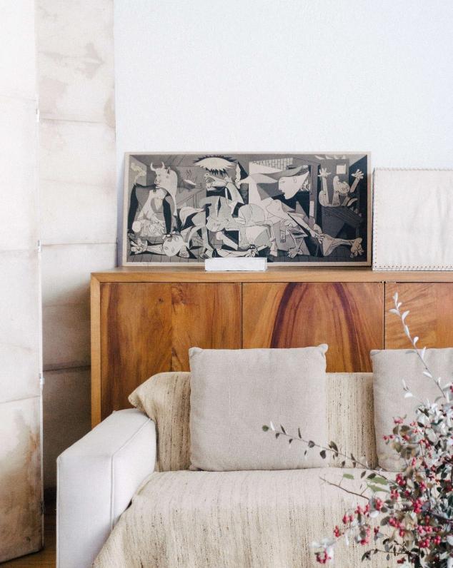 Guernica di Picasso sopra ad una madia in stile moderno con divano bianco
