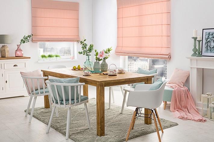 sala da pranzo con tavolo in legno massello, sedie bianche e tende rosa
