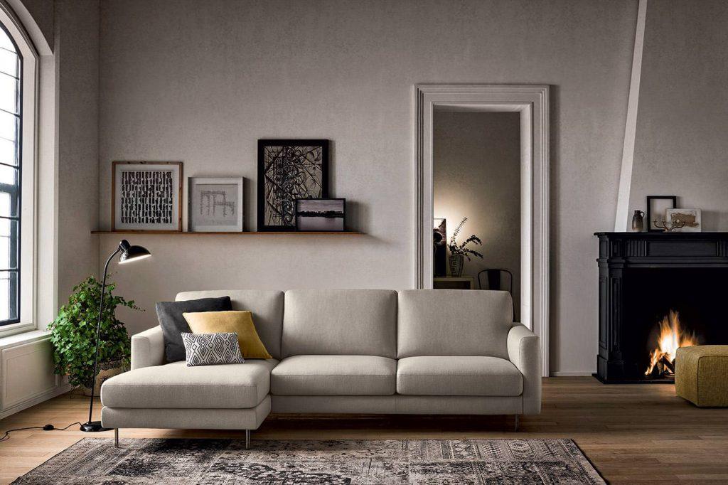 divano ad L grigio chiaro contro parete a calce bianca con camino