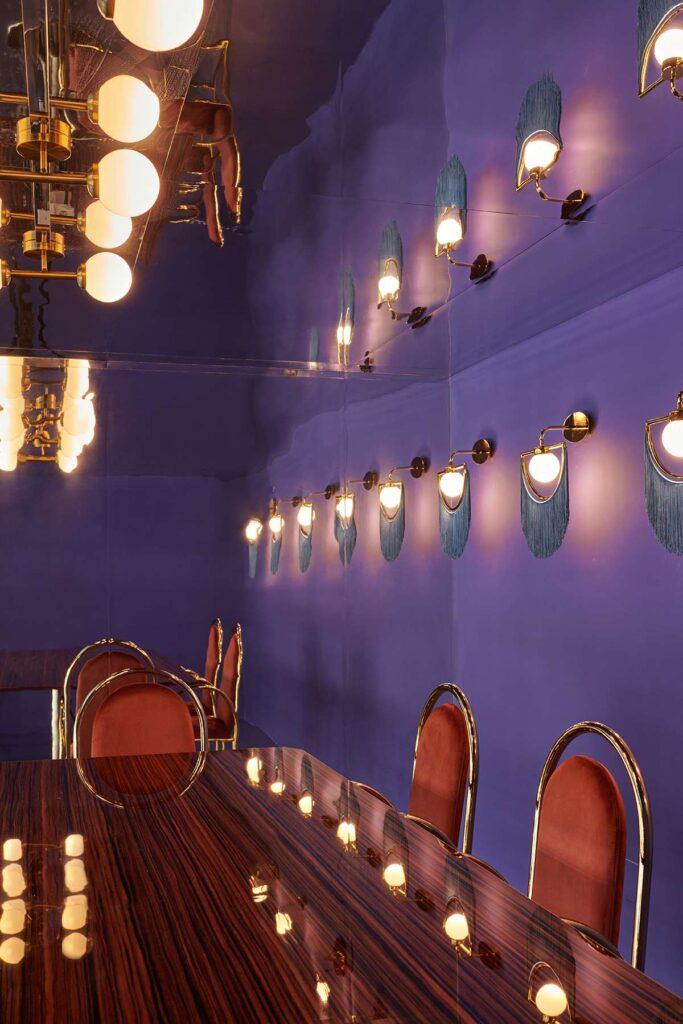 esempi di coworking innovativi: una delle sale riunioni con pareti viola e sedie Arco di Houtique