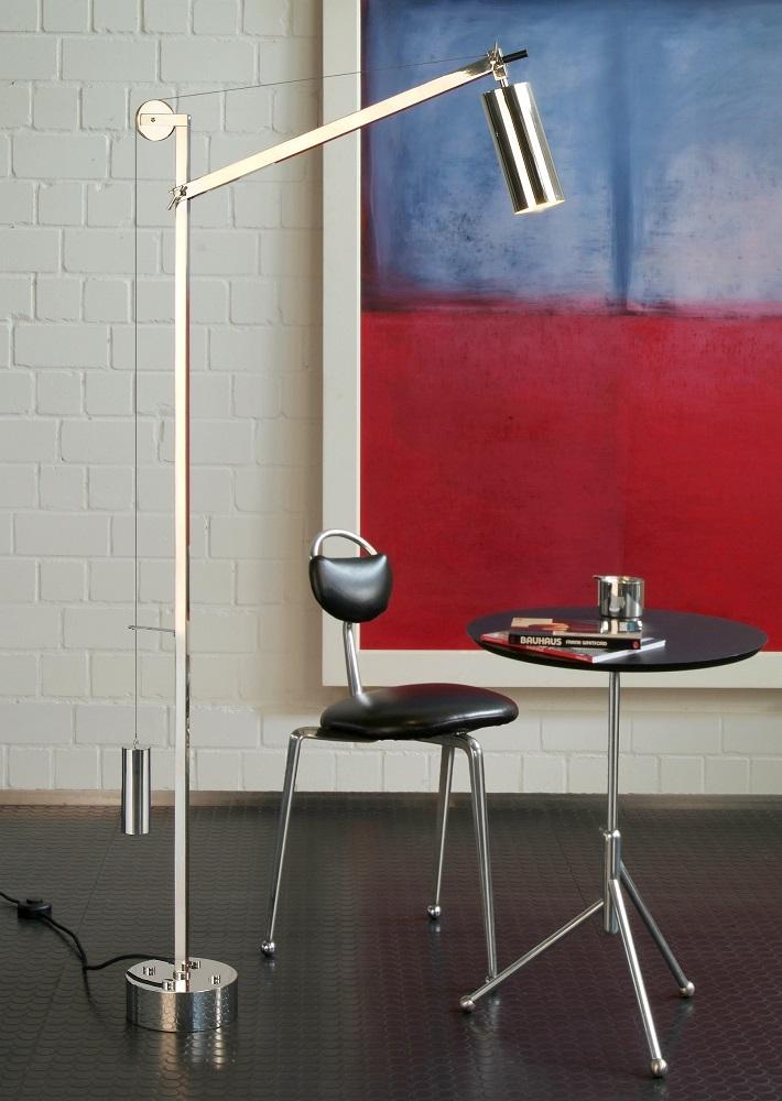 pavimento in vinile, sedia in acciaio e cuoio nero, tavolo in acciaio e lampada da terra in acciaio con quadro astratto