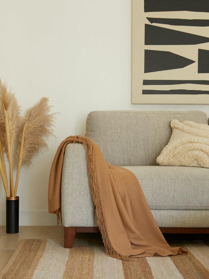Materiali ecosostenibili per il design in un soggiorno con divano grigio, tappeto a righe ed erba pampa.