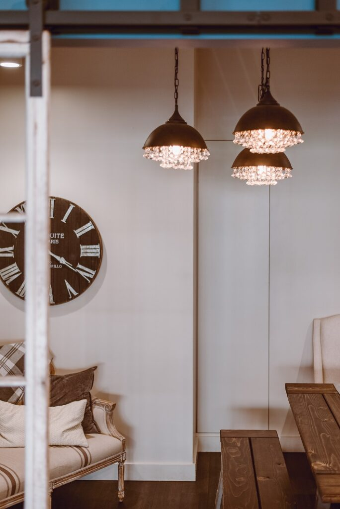 materiali ecosostenibili per il design: scala in legno con lampadari a goccia e poltrona classica