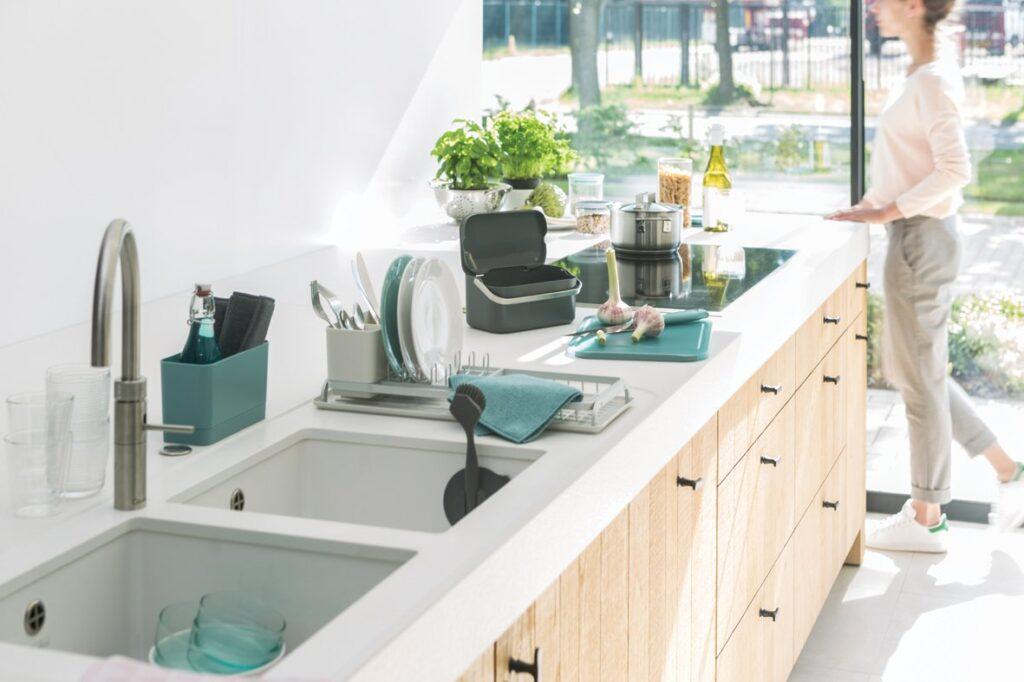 cucina senza pensili, in rovere e top bianco con utensili per pulizia