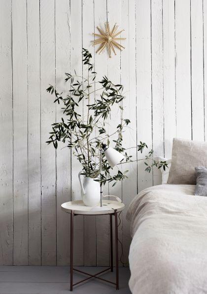 camera da letto con parete in legno bianco gesso, piante e letto con copripiumino bianco