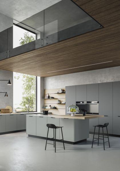 Cucina componibile moderna in grigio chiaro, con isola con fuochi e tavolo per colazione sotto soppalco in legno di olmo